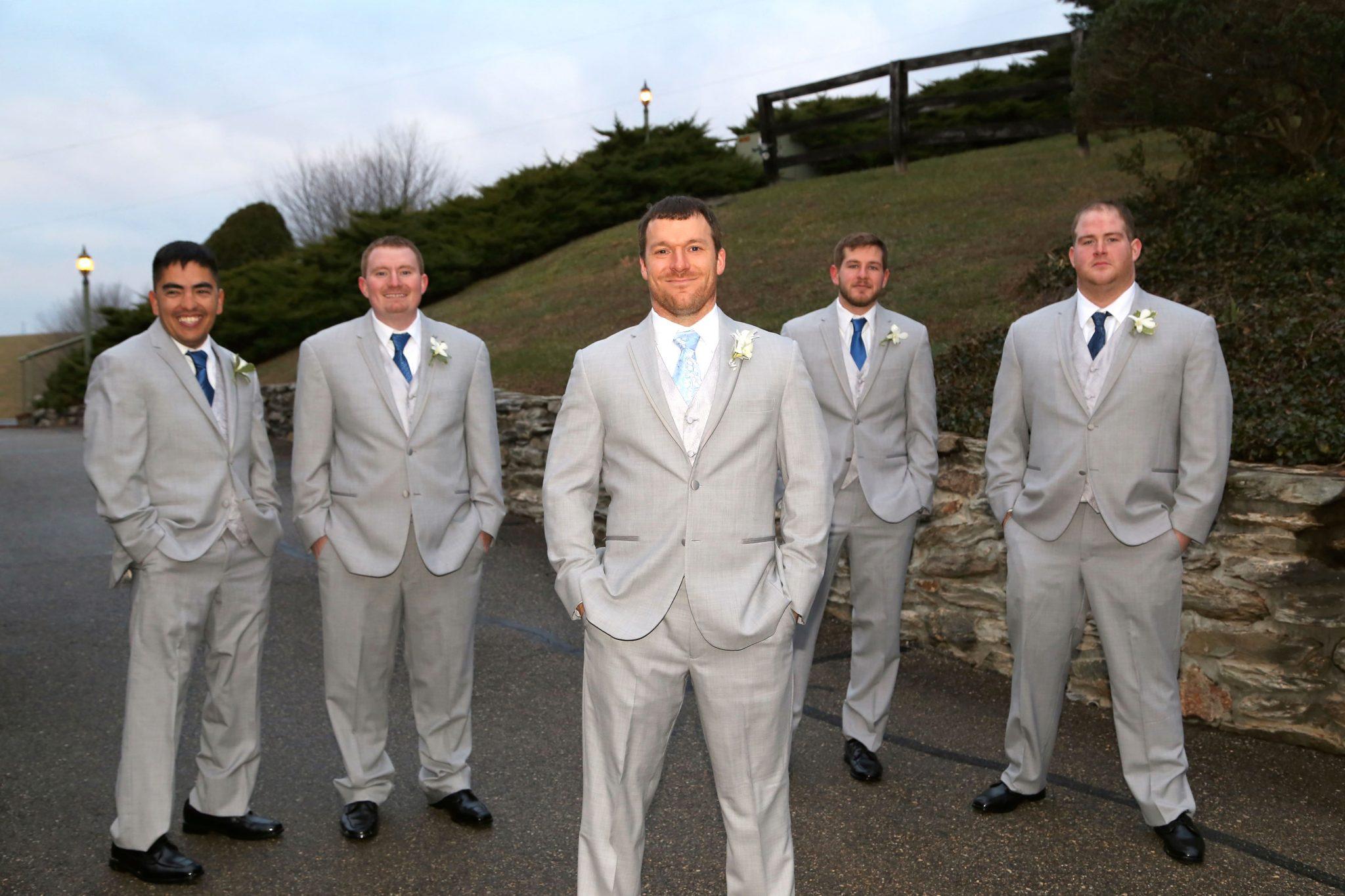 Groom poses steps from groom's room before indoor wedding