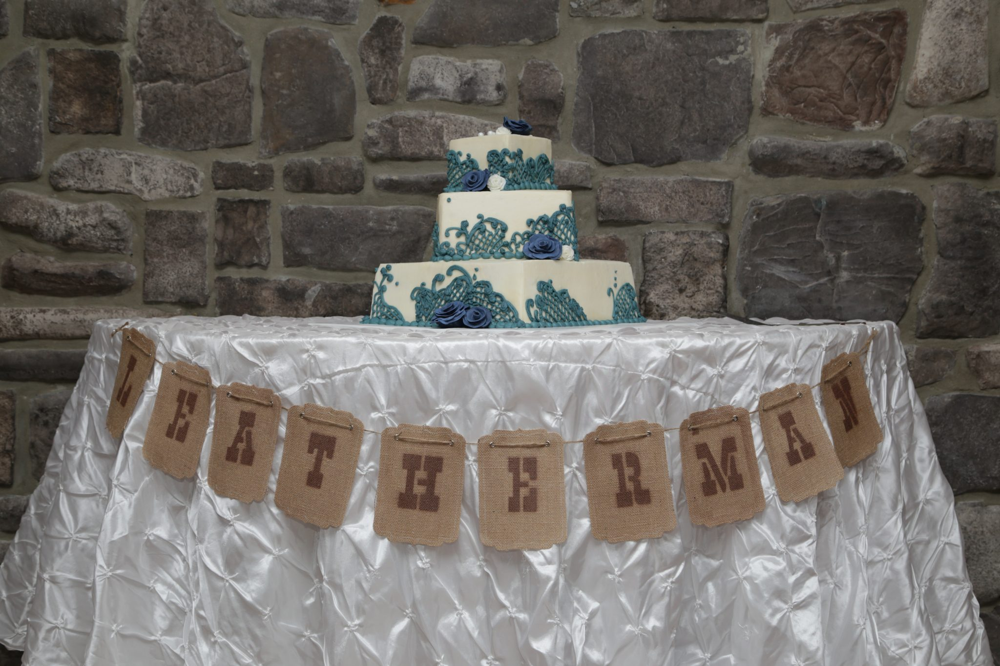 Wedding cake table is decorated with married couple's name for their country wedding in Maryland.