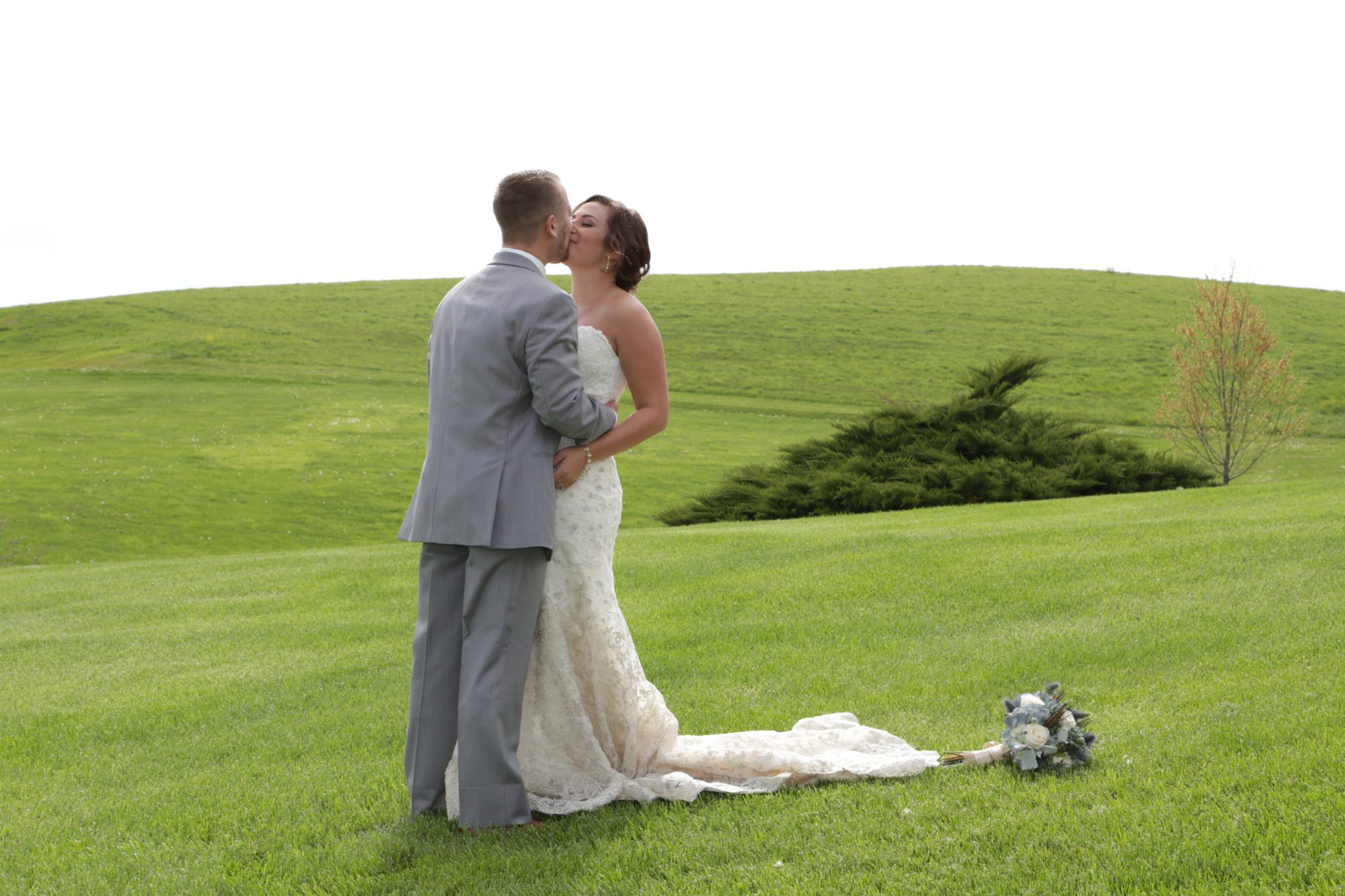 Bride and groom kiss on the lawn after their April country wedding