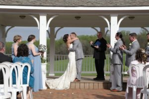Kissing after April country wedding outdoor wedding ceremony