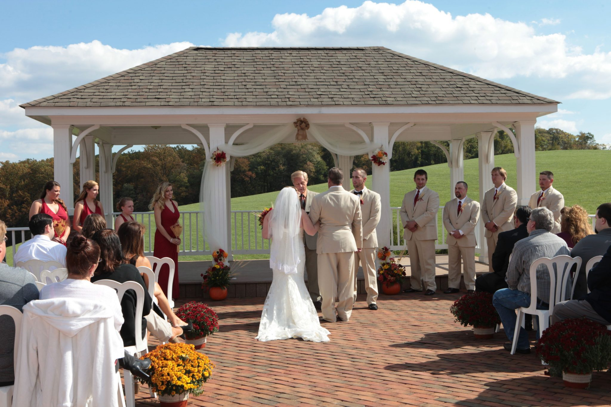 Outdoor wedding ceremony is held on covered pavilion