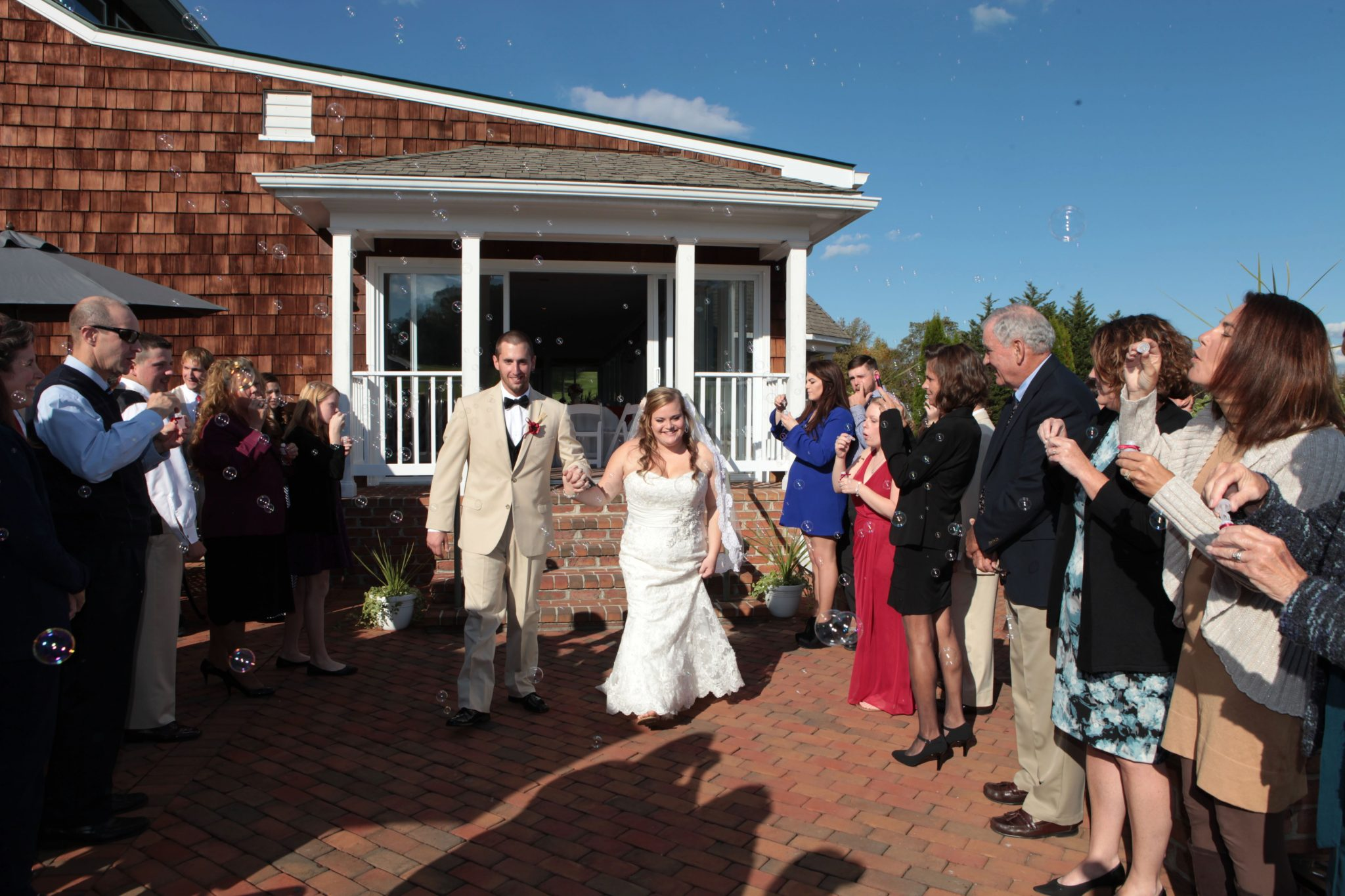 Couple walks from outdoor wedding pavilion after vows