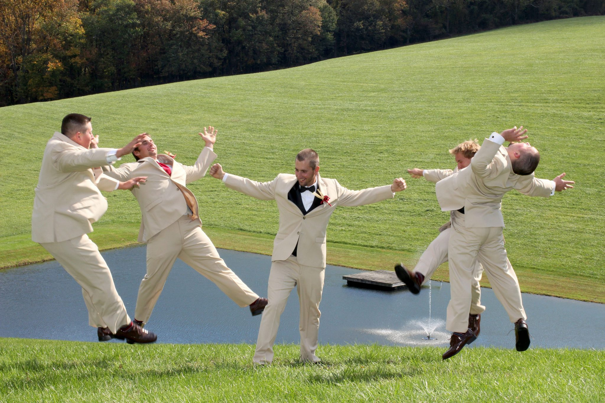 Groomsmen pose by pond on back lawn of private estate near Hagerstown Maryland