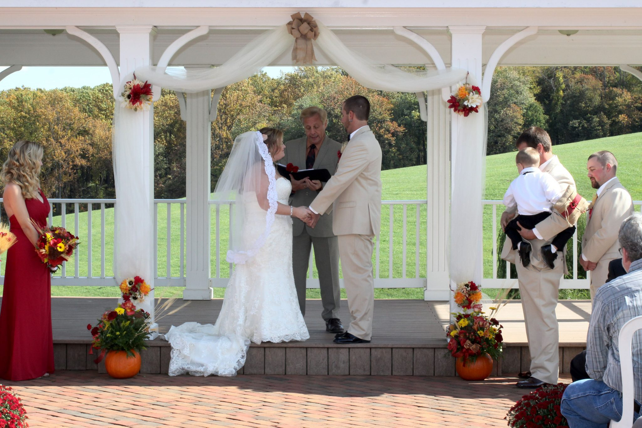 The couple exchange vows on the outdoor pavilion on a gorgeous fall day