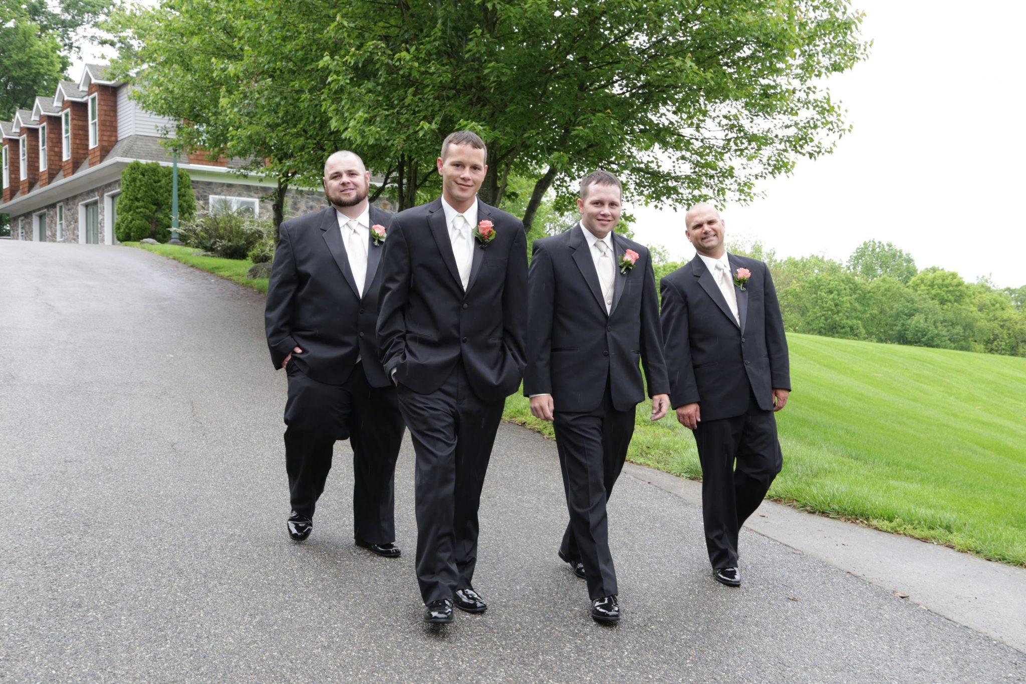 Groom and groomsmen on driveway outside of grooms room