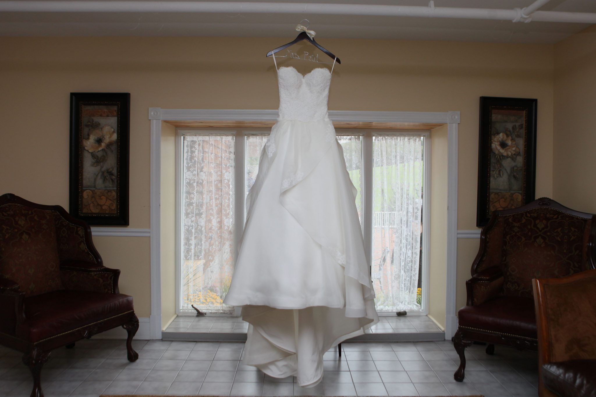 Bride's dress hangs in the bride's room before the wedding ceremony.
