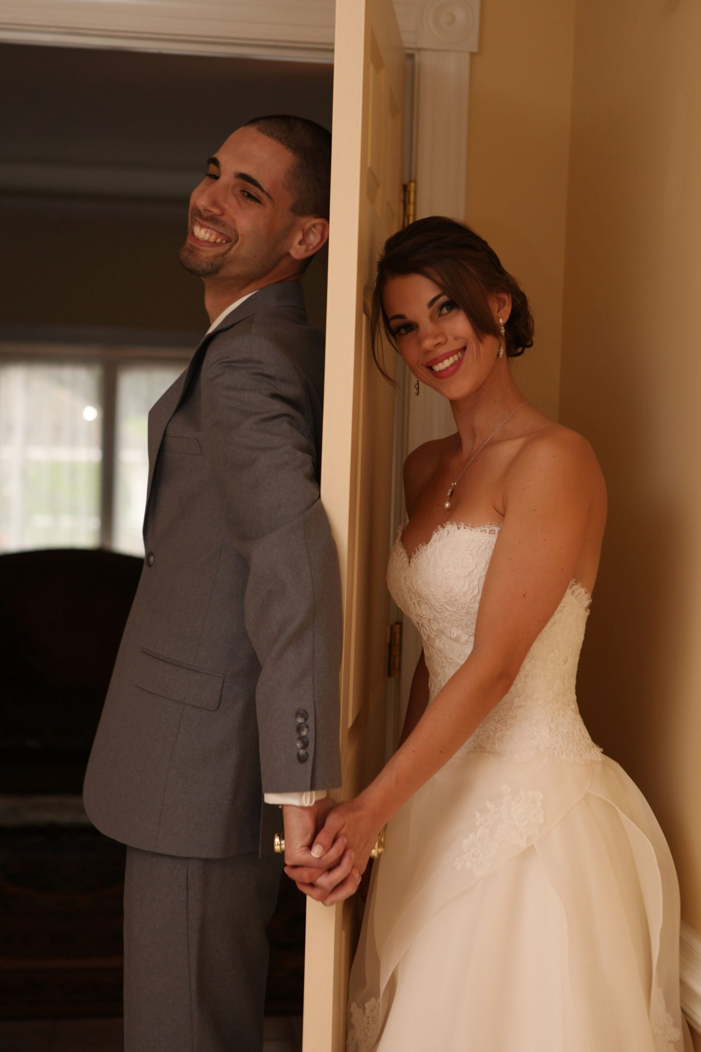 Bride and groom stay on opposite sides of door before wedding ceremony in this fun photo.