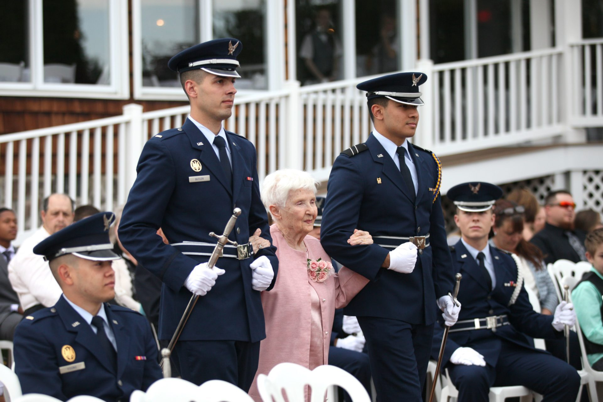 Grandmother escorted by military during tea party theme wedding
