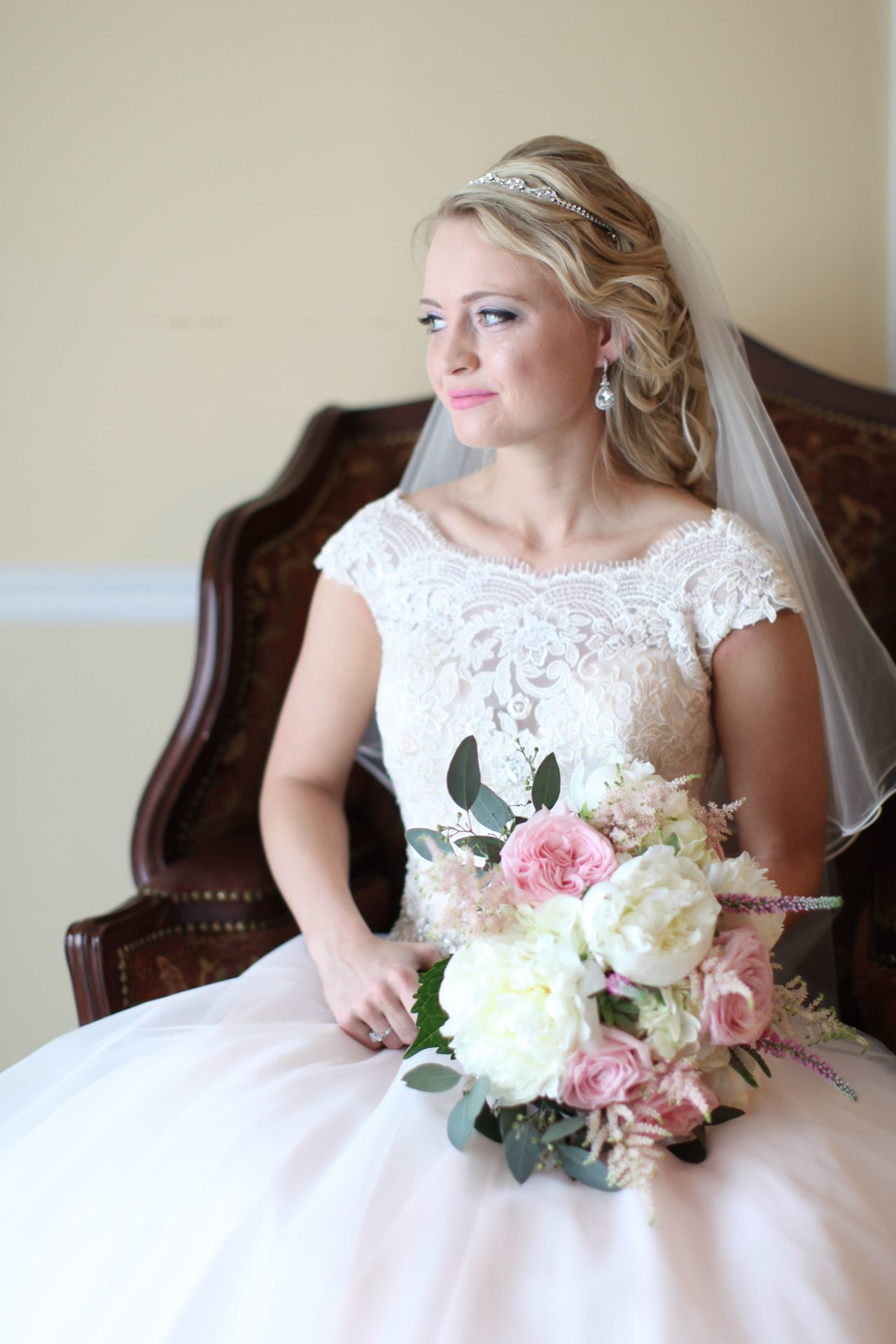 Bride poses in victorian chair in brides room at Morningside Inn