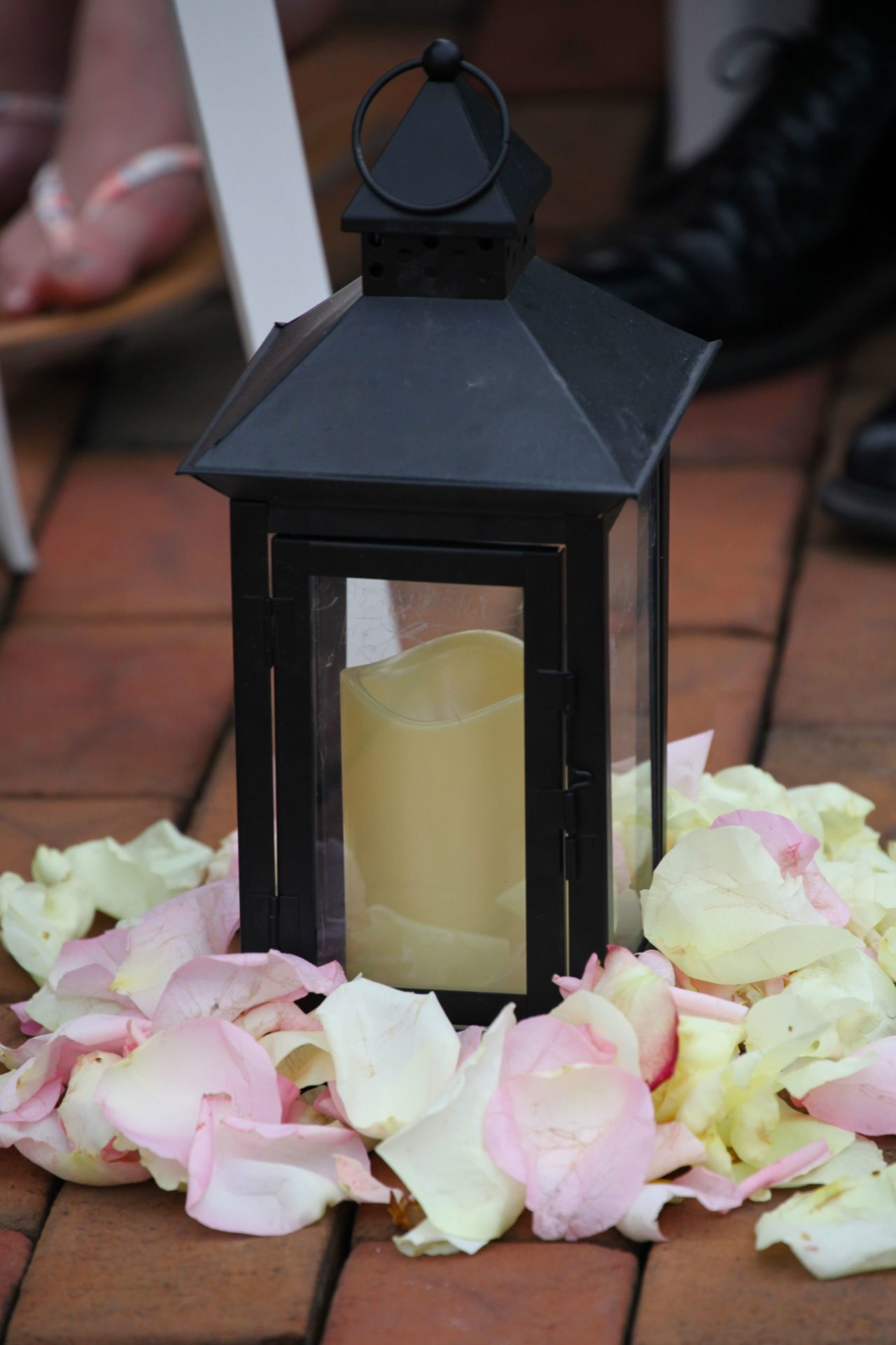 Rose petals around candle to decorate wedding ceremony aisle