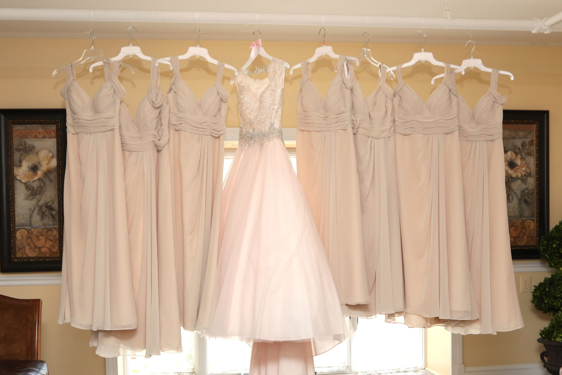 Wedding dress and bride's maid dress hang in the brides room at Morningside Inn wedding venue in Frederick Maryland
