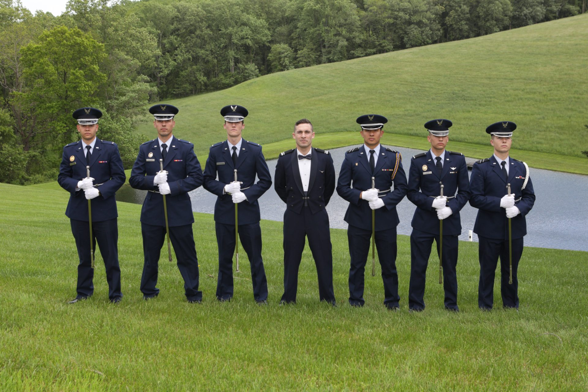 Military wedding, groom poses with groomsmen on lawn by pond at Morningside Inn