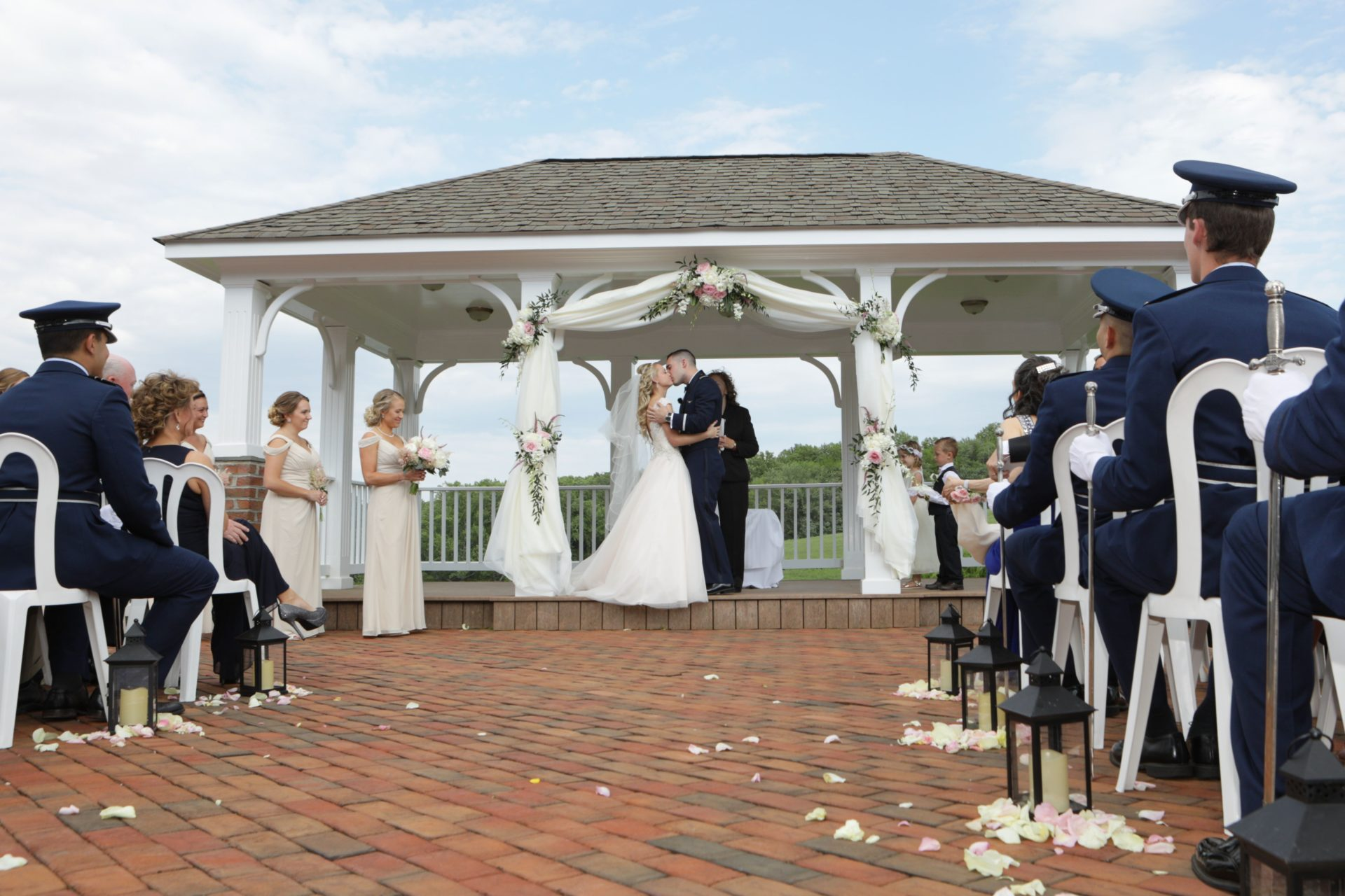 Bride and groom kiss on pavilion after outdoor wedding ceremony in Maryland