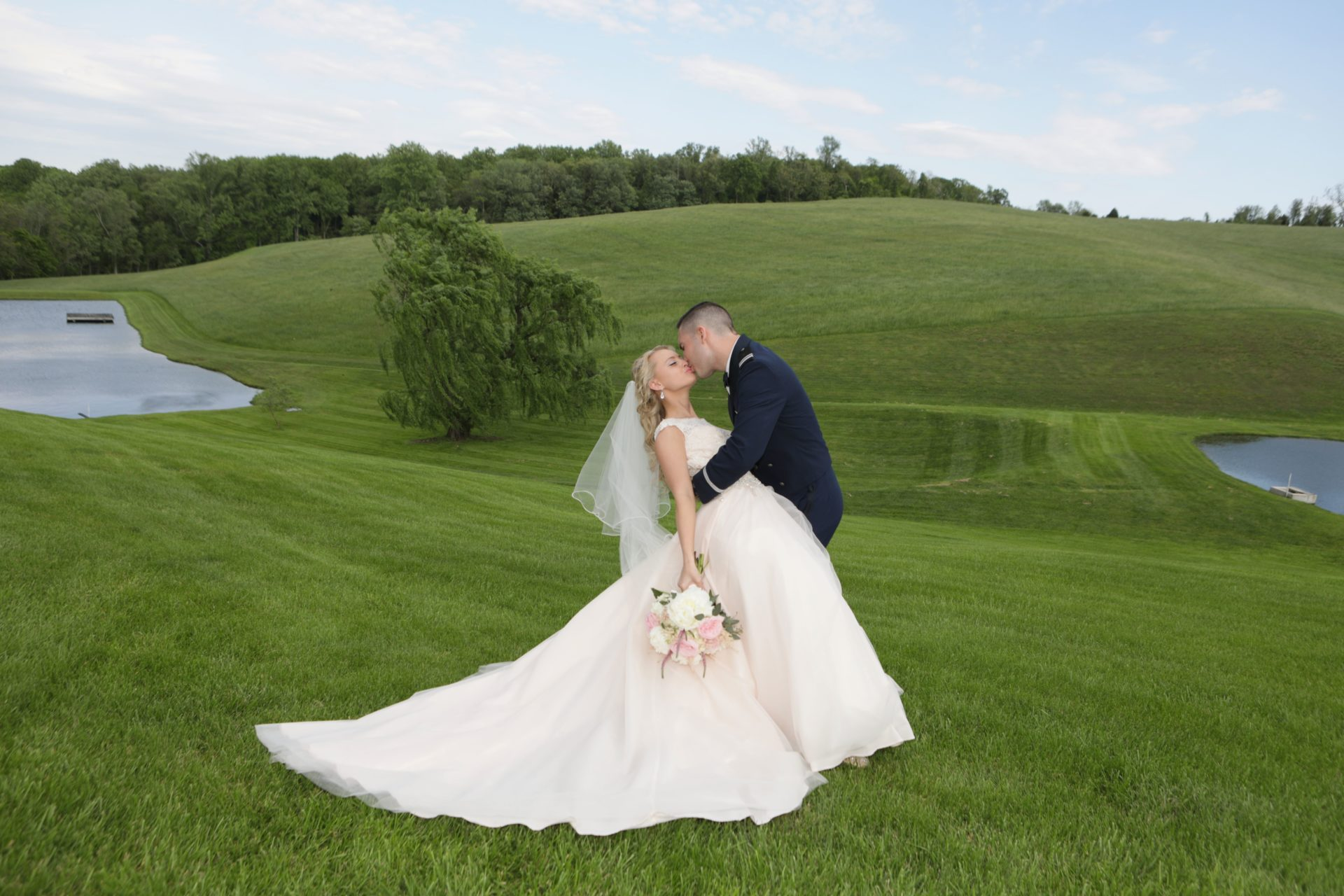 Bride and groom kiss on lawn between two ponds at Morningside Inn