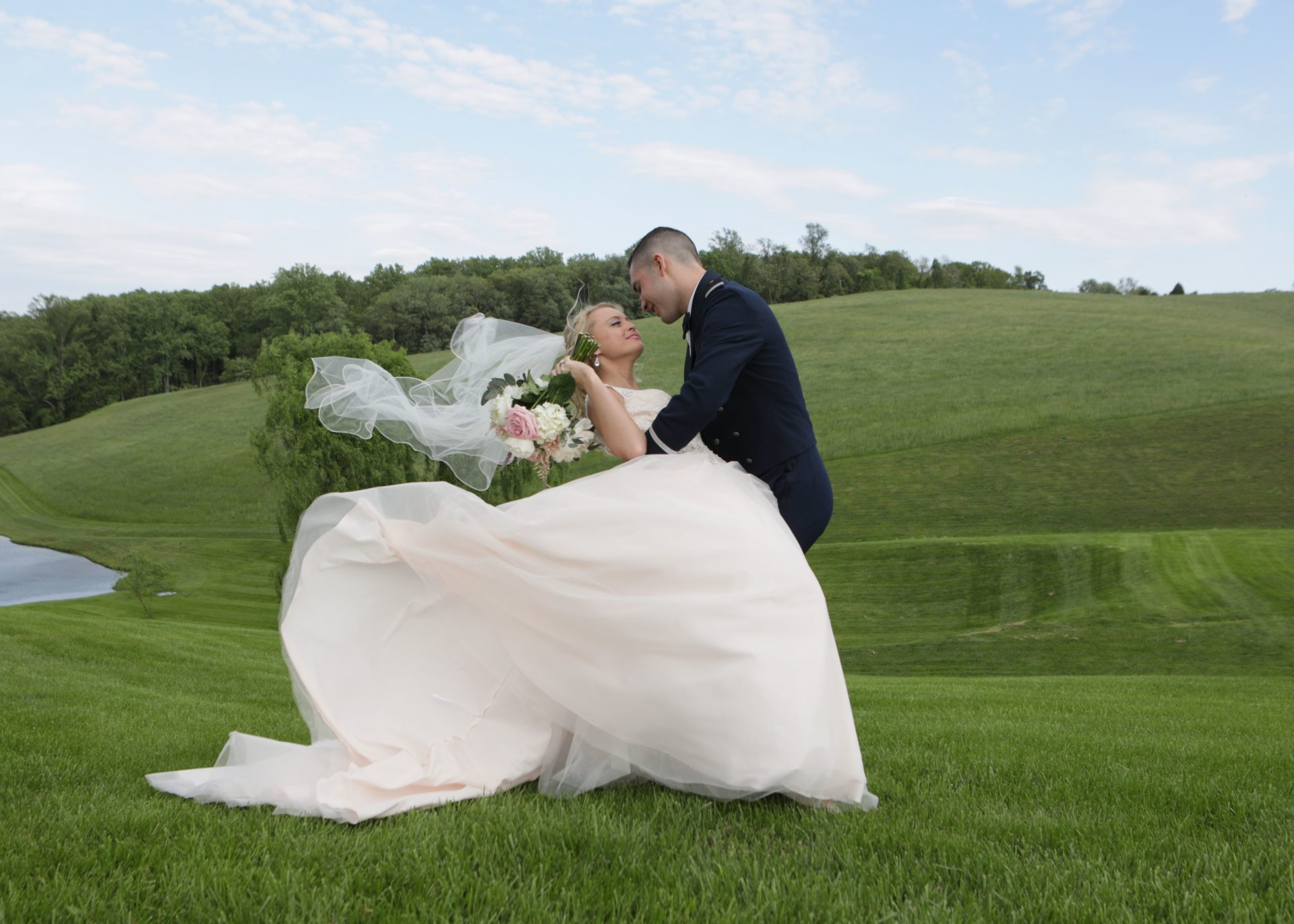 Bride and groom pose on lawn by pond at Morningside Inn with breeze lifting veil.