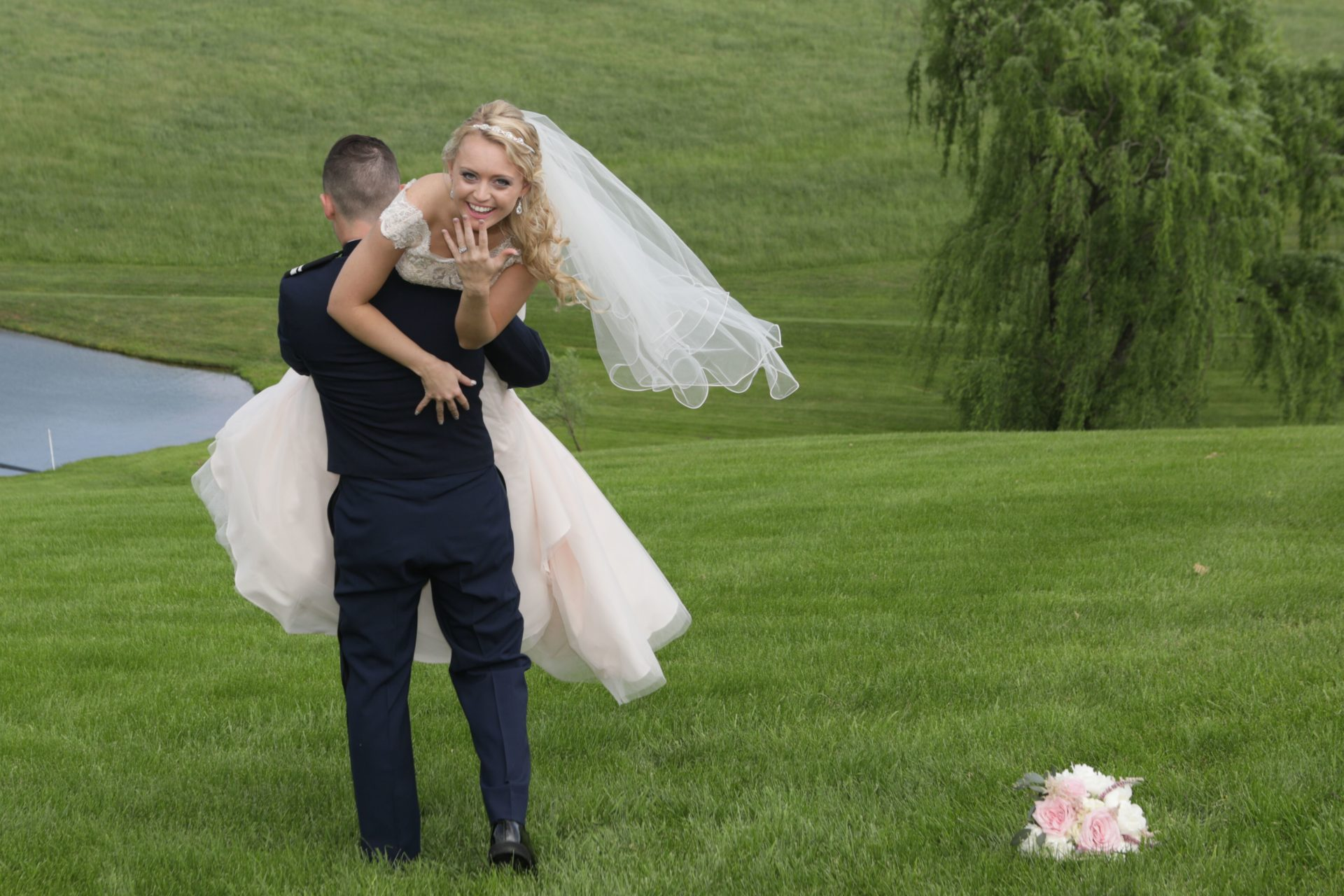 Groom carries bride away on back lawn at Morningside Inn wedding venue