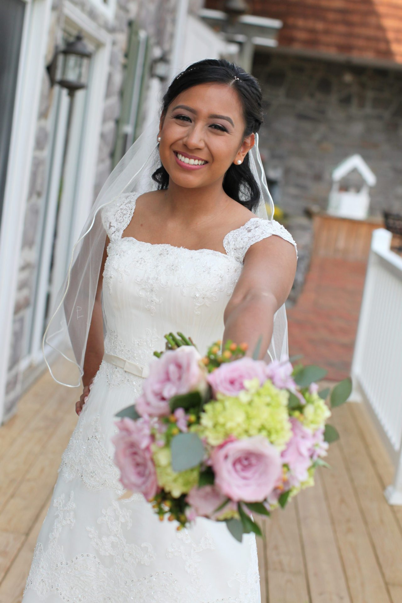 Bride poses with bouquet on back deck at Morningside Inn