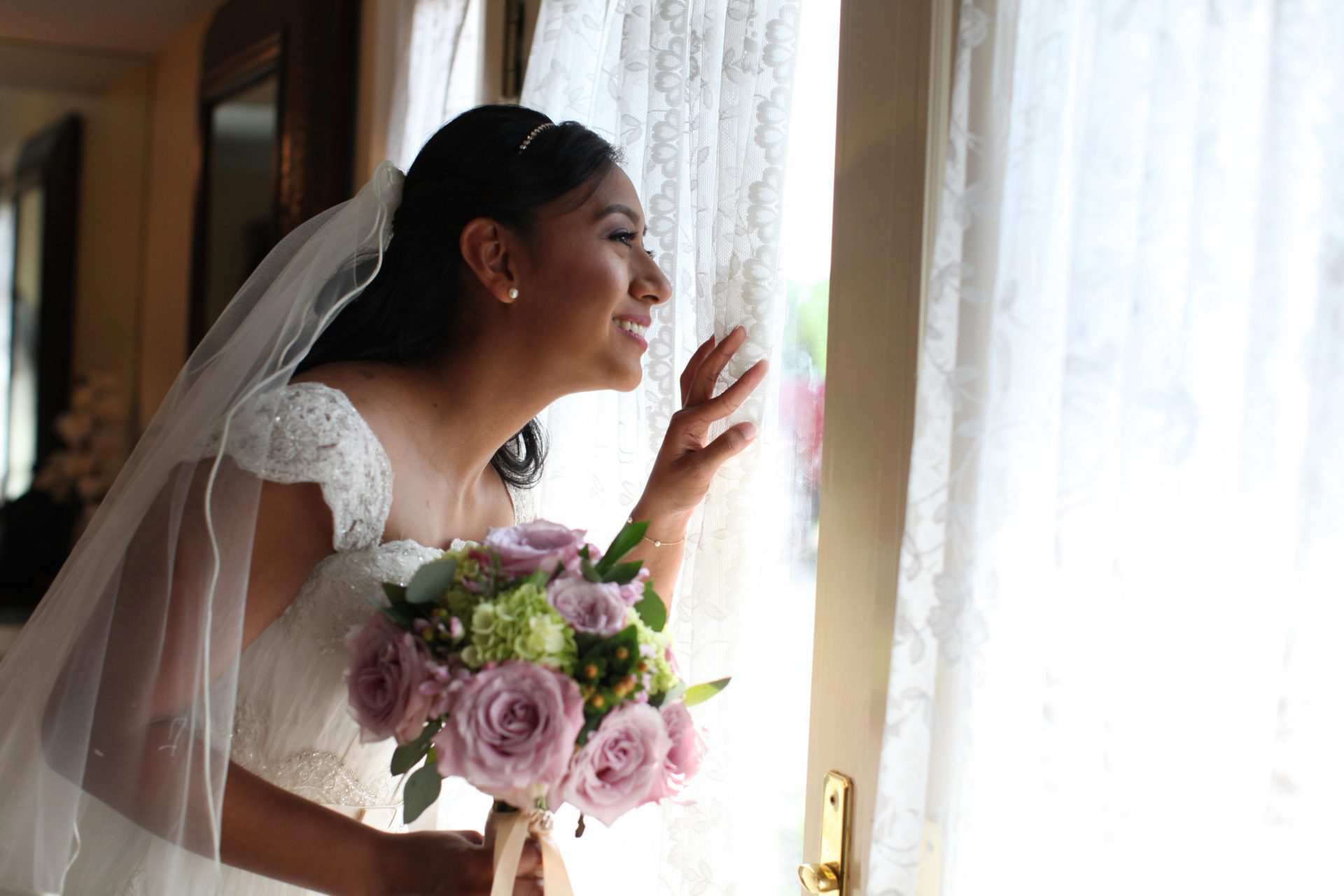 bride looks out window before outdoor wedding ceremony at Morningside Inn