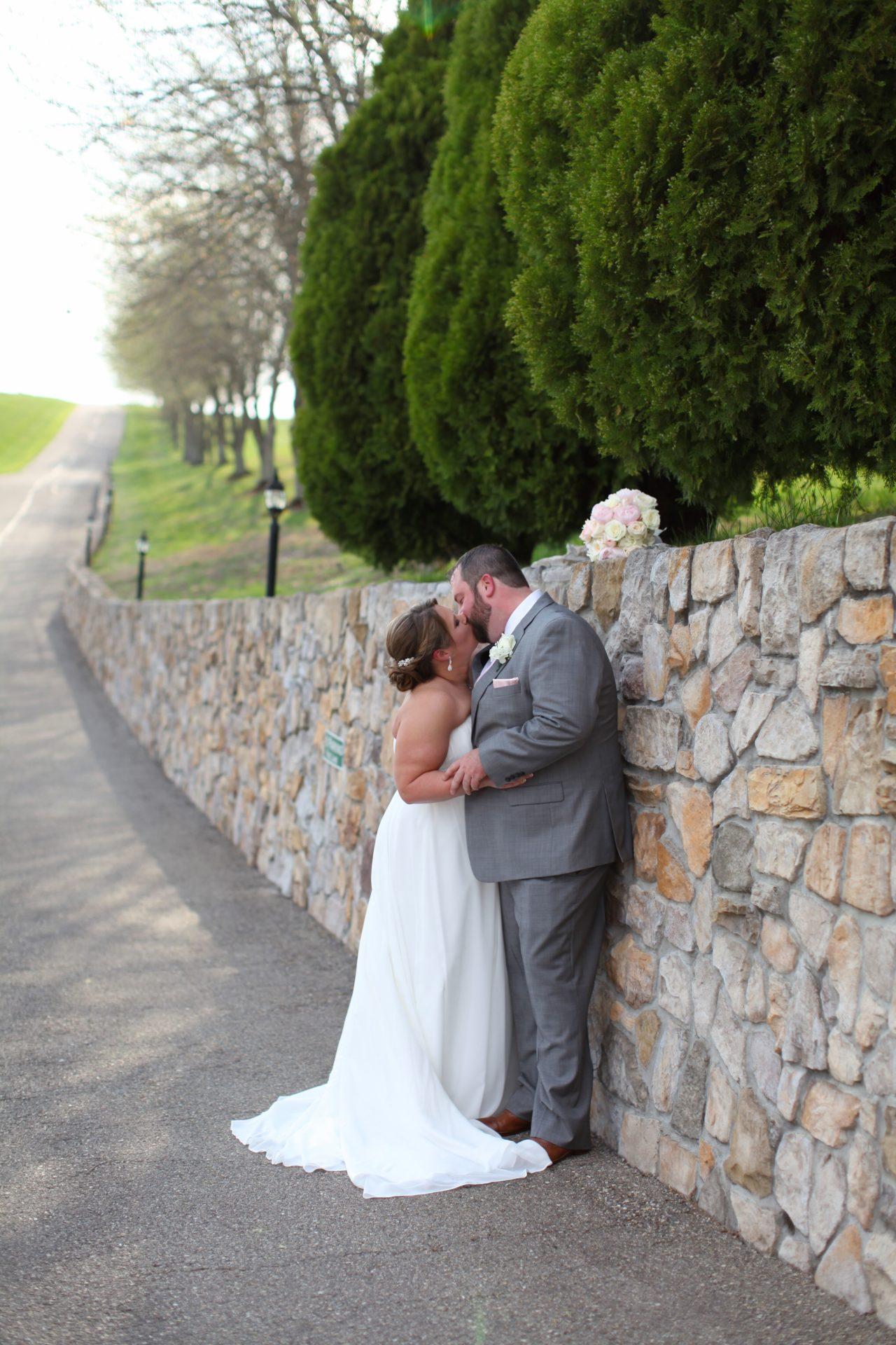 kiss by stone wall Sam & Amy's Wedding April 15 2017