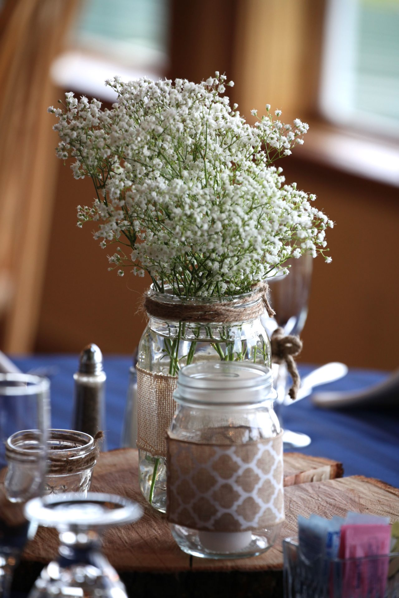 Simple rustic wedding centerpiece with glass jar and baby's breath flowers