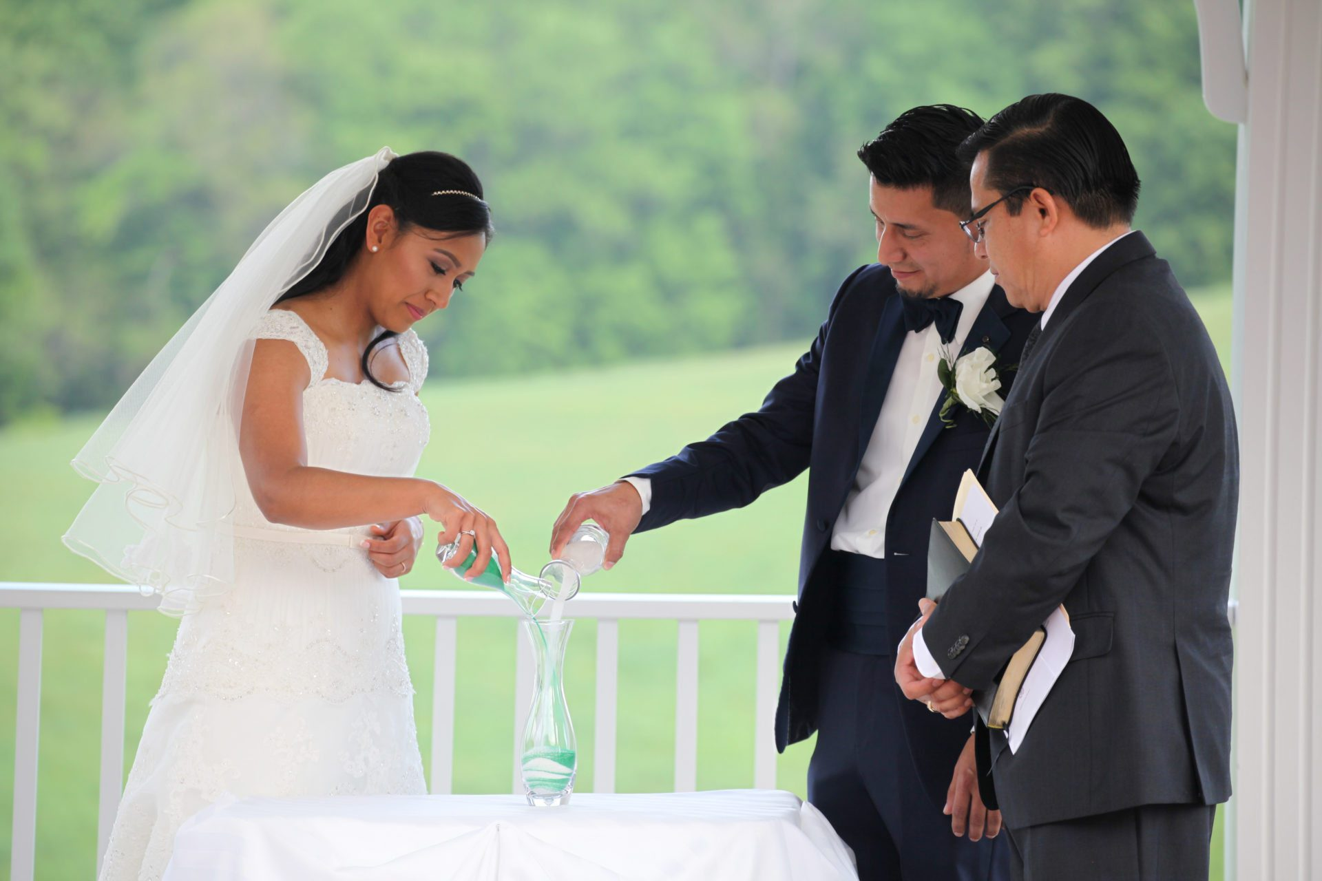 Bride and groom pour unity sand during outdoor wedding ceremony at Morningside Inn wedding venue Frederick MD