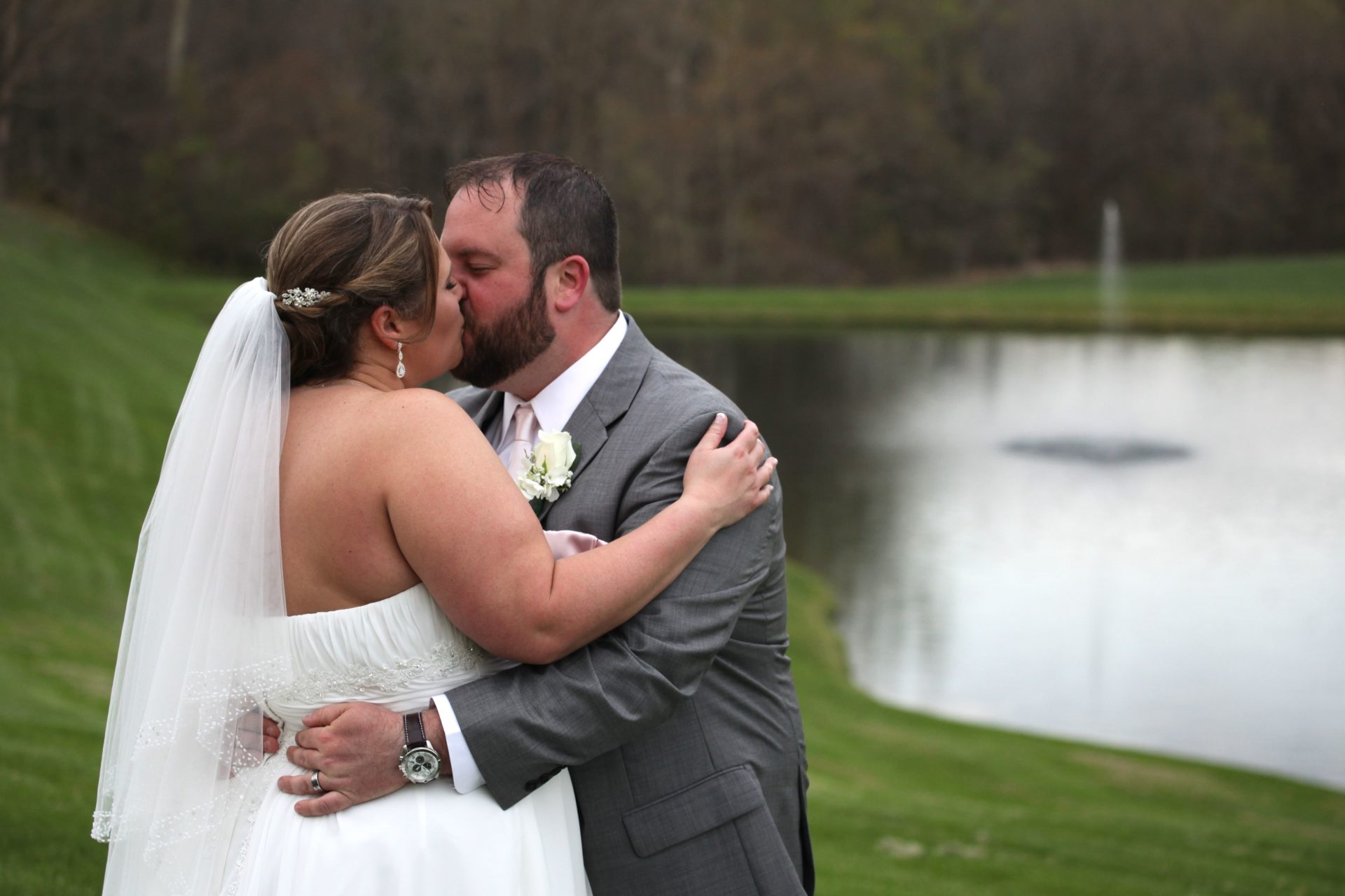 Bride and groom kiss by pond