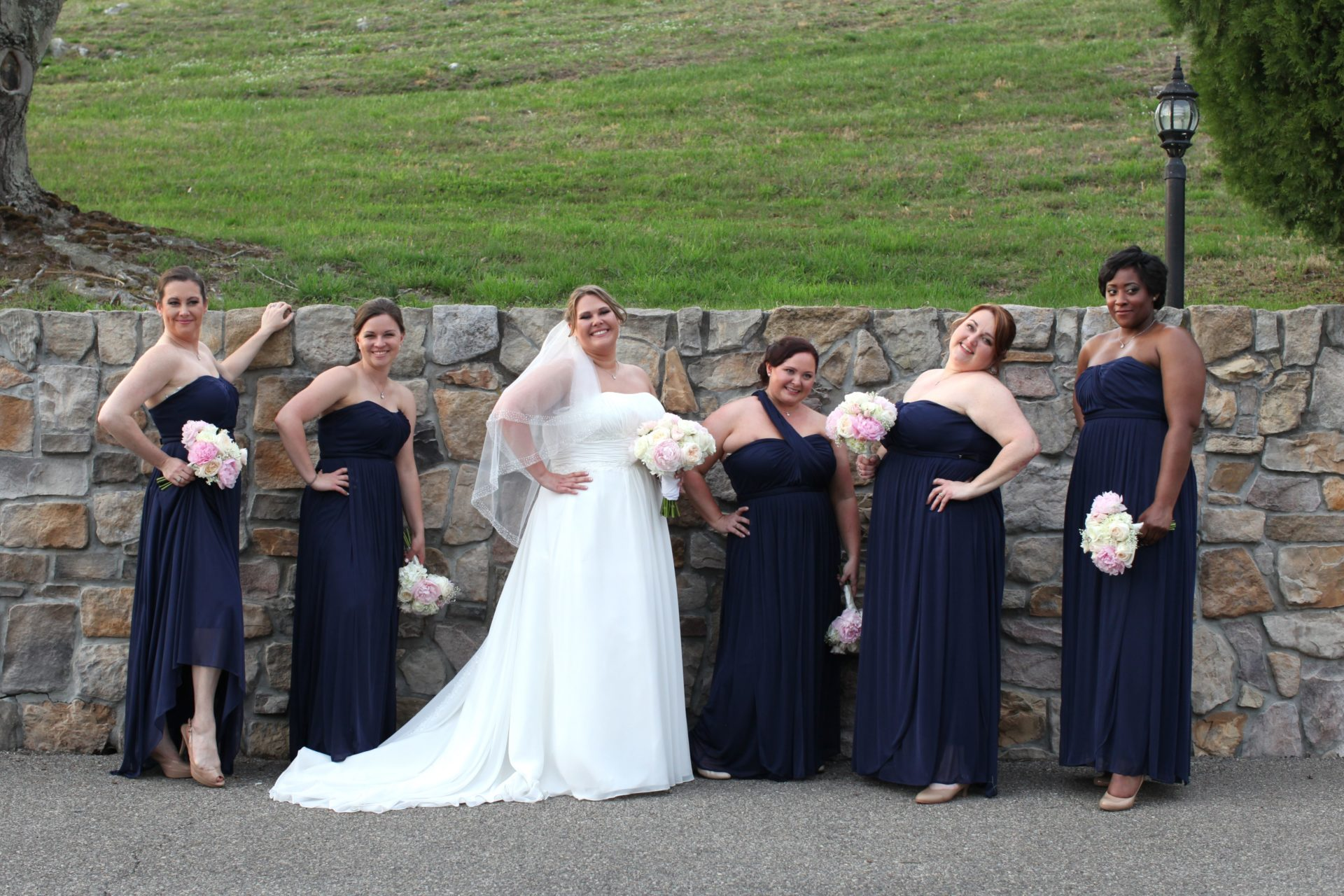 Bridesmaid and bride in front of stone wall