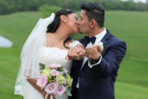 Bride and groom show rings while kissing in back field of Morningside Inn wedding venue in Frederick MD