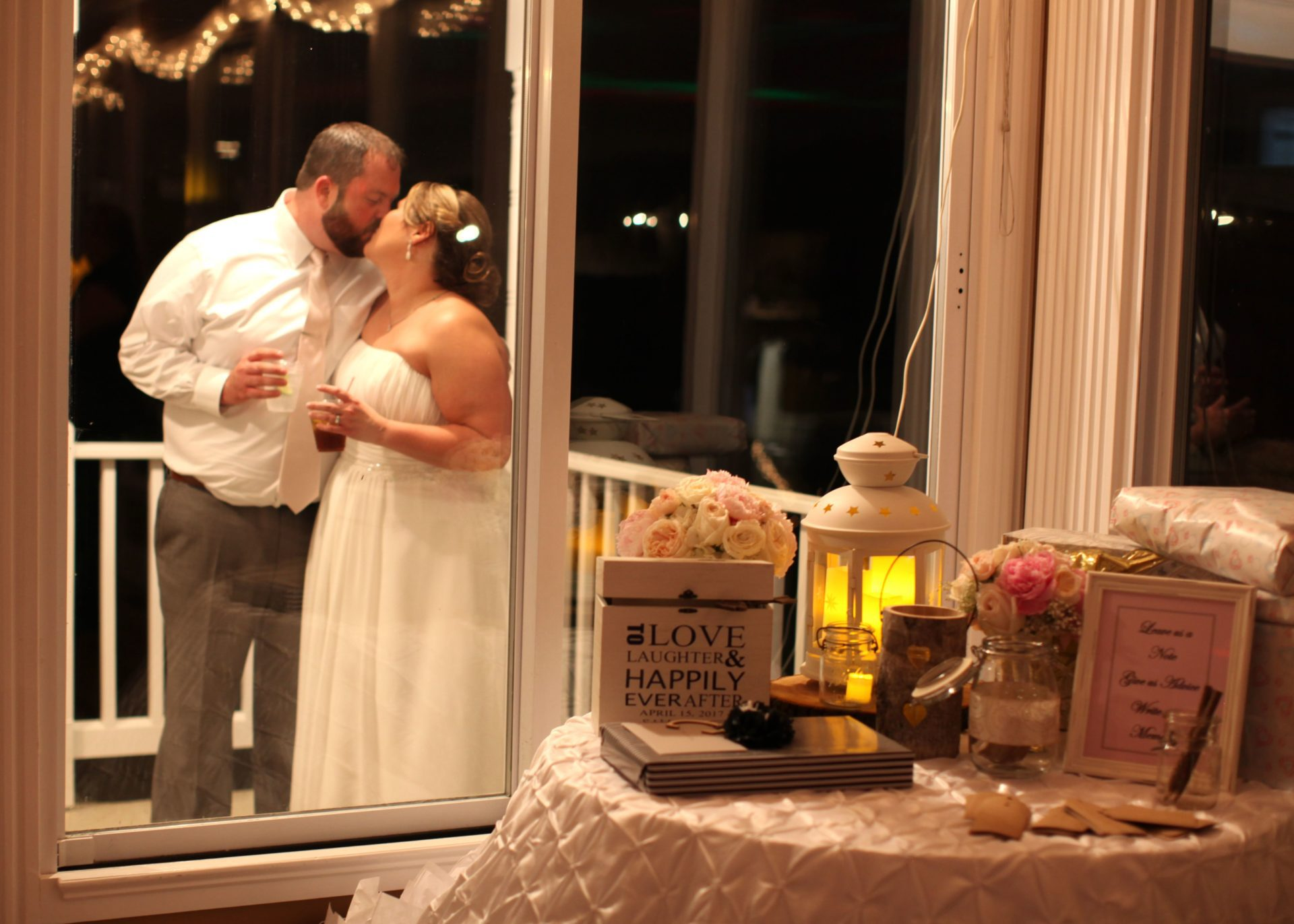 Bride and groom kiss outside reception room window