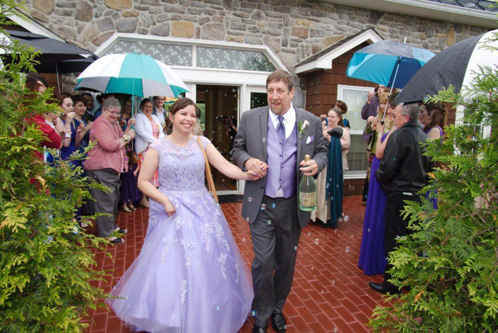 Bride and groom leave Morningside Inn in rain after wedding ceremony.