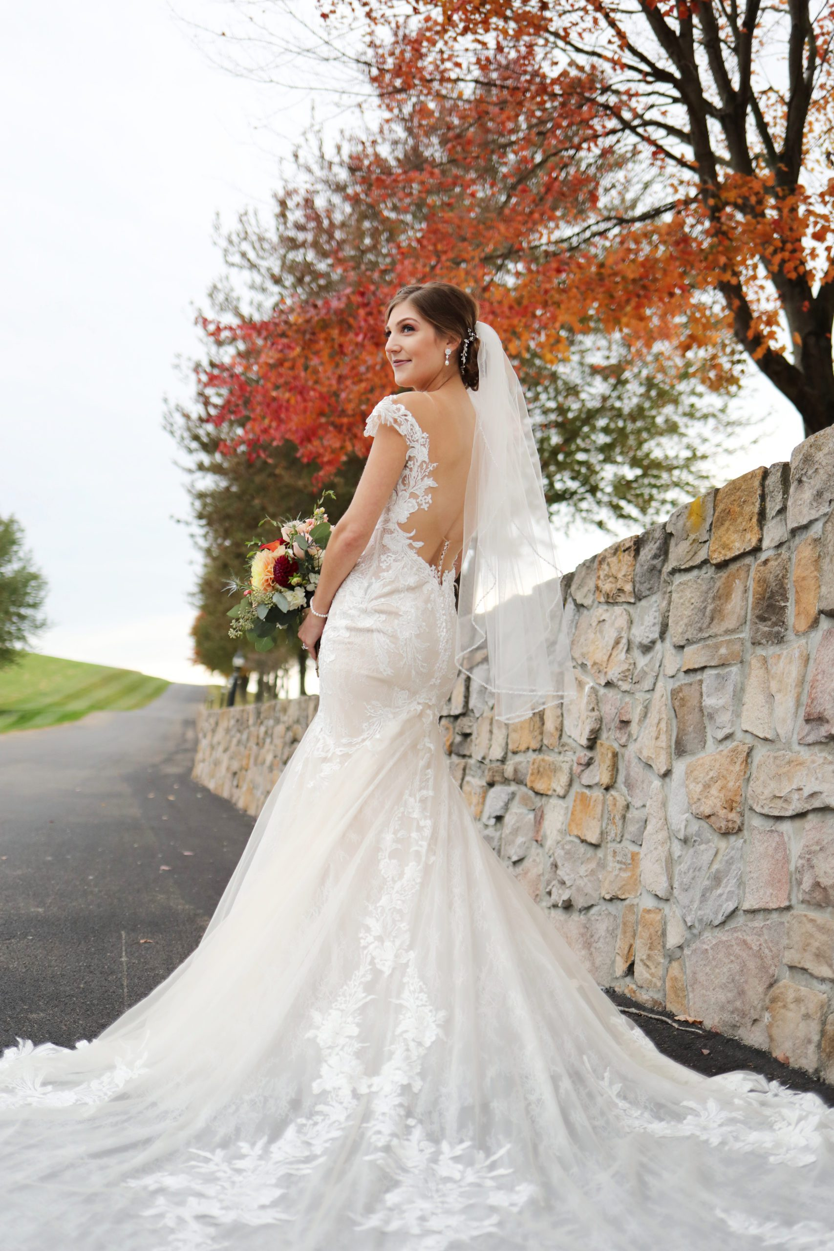 Bride stands by stone wall at Morningside Inn Wedding venue in frederick private estate